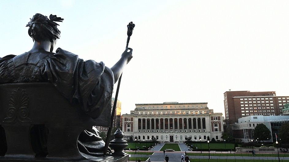 Bronze statue of Alma Mater, a classically-dressed woman sitting with a laurel wreath in her hair and a scepter in her hand, against the backdrop of Butler Library on Columbia's Morningside campus.