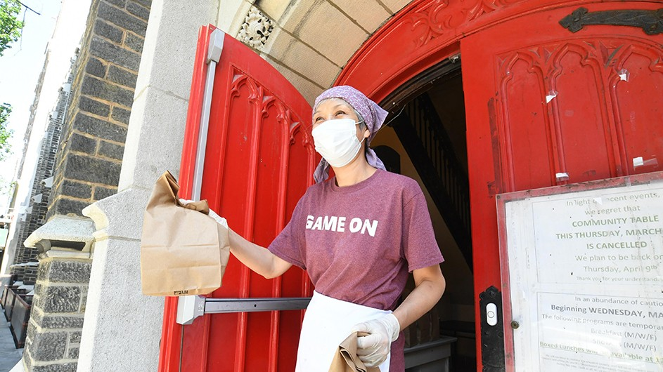 A woman with a bandana and a mask stands in front of an open red door, offering a bag of food.