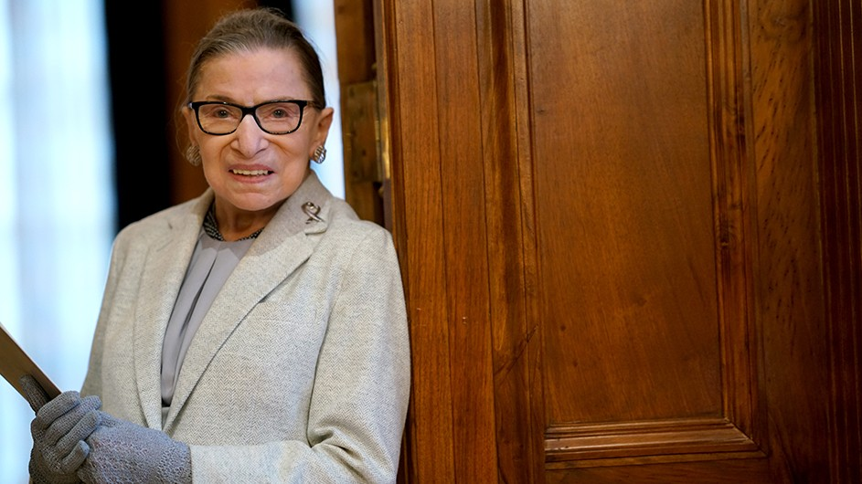 Ruth Bader Ginsburg, a light-skinned woman with dark hair and glasses, against the backdrop of a medium brown wood door.