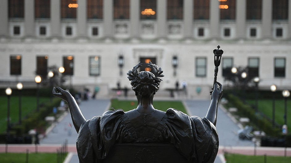 a view of the back of alma mater, a bronze statue of a woman with a laurel crown on her head and a scepter, in front of butler library, a classical building.