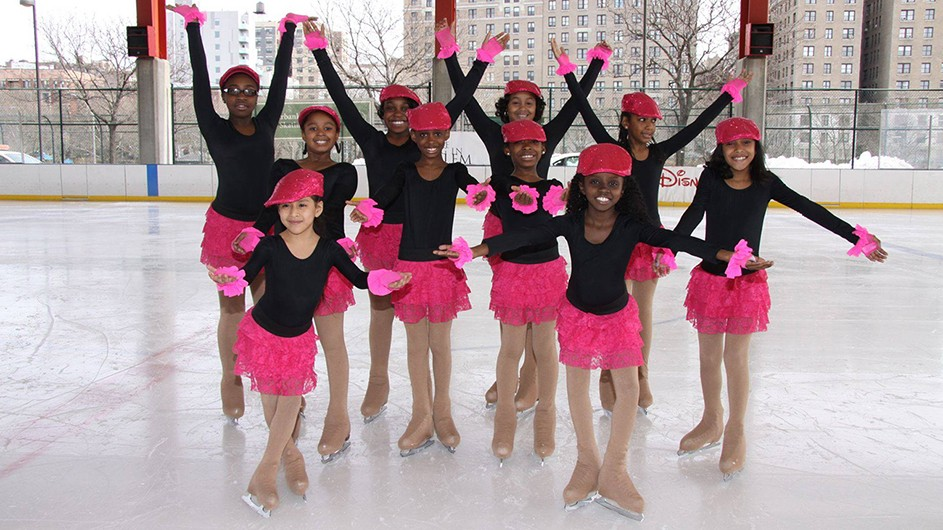 A group of kids posing on an ice rink in pink skirts and black leotards on skates.