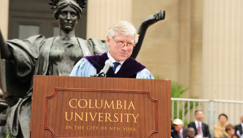 President Lee C. Bollinger at the podium in front of Alma Mater statue at commencement in 2016
