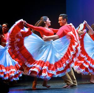 Dancers in red spin around in a performance of Sabor Latino at the Miller Theater