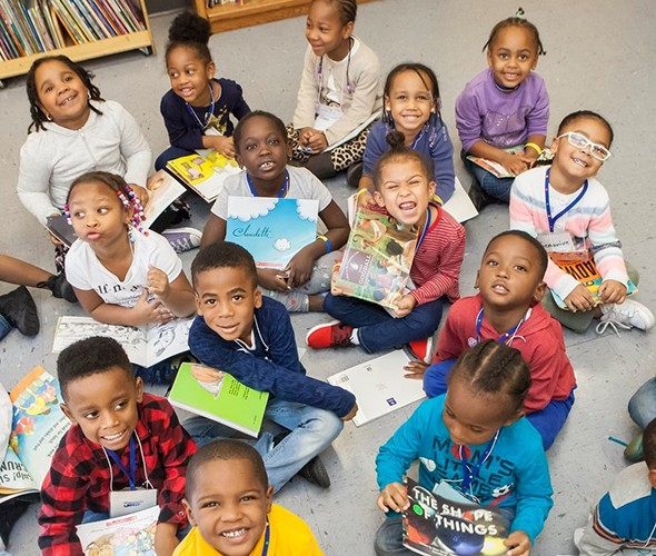 A group of kids lifting their heads up from their books to smile and pose for the camera