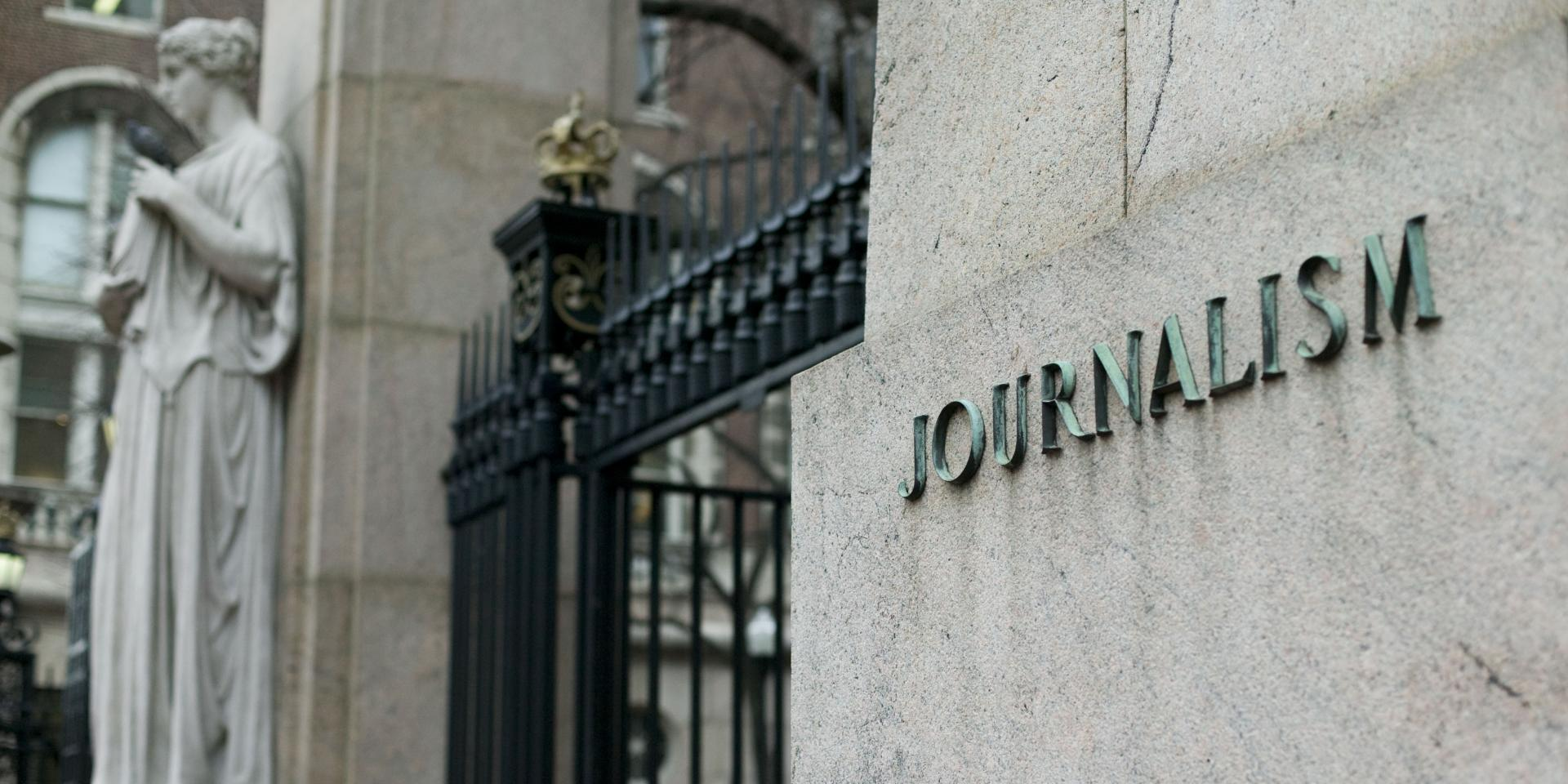 "A close up view of the journalism building outside Columbia's Main Gate, with a statue in the background and the word ""journalism"" inscribed on the building in the foreground."
