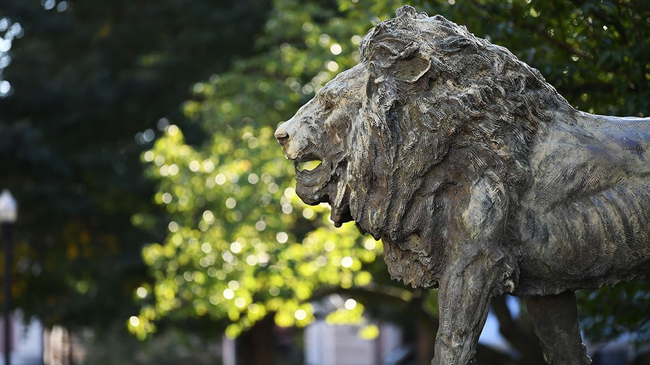 A gray stone statue of a lion, against a backdrop of green foliage.